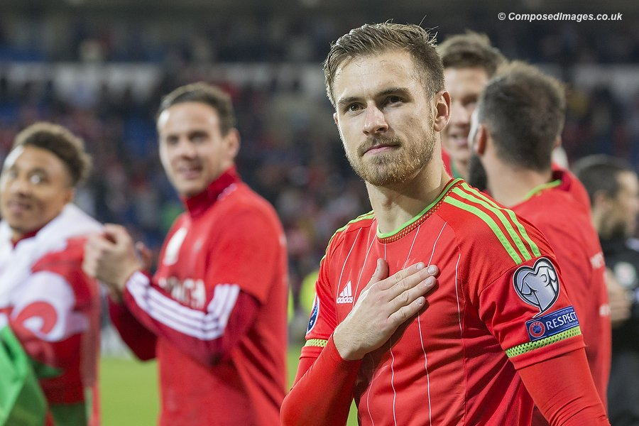 Aaron Ramsey touches the Wales crest on his jersey during a lap of honour to thank the fans at the end of the UEFA Euro 2016 qualification match between Wales and Andorra at Cardiff City Stadium, 13/10/15.